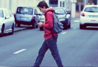 Pietonii care se uita in telefon atunci cand traverseaza strada ar putea fi amendati