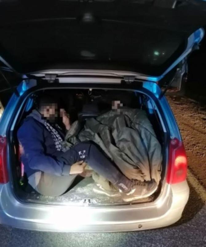 Ungaria. Șofer român, încătușat de polițiști, după ce a fost prins cu migranți, ascunși în portbagaj